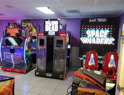 Arcade interior with Jurassic Park game, Walking Dead game, Space Invader